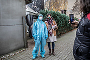 A woman posses for a photo with a medical staff member in a protective suite and mask after a covid-test at a covid-19 test station outside the Kitkat night club in Berlin, Germany, December 13, 2020. Berlin's world famous KitKatClub has initiated a fast covid-19 tests operation in its premises People are able to set an online appointment and arrive to have a covid antigen rapid test swab test in what was reported by local media outlet as the lowest price in the German capital. The club itself is closed since early 2020 due to the health restrictions imposed on cultural venues in Germany.