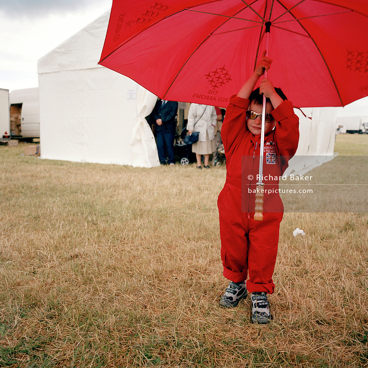 Young wannabe of the Red Arrows, Britain's RAF aerobatic team, holds up an RAF merchandise brolley during airshow.