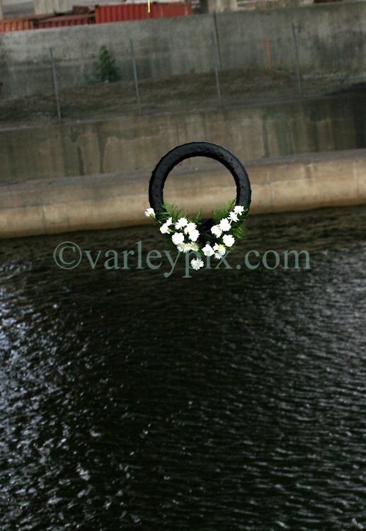 29 August 2006. New Orleans, Louisiana. Lower 9th ward. Great Flood commemoration and memorial ceremony; to 'honor and remember our loved ones who have passed.' <br /> The memorial wreath in mid air as it falls to the industrial canal beneath the bridge, close to the levee breach which destroyed the Lower 9th ward. The wreath was dropped from the bridge into the water.<br /> Photo Credit©; Charlie Varley/varleypix.com