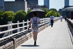 © Licensed to London News Pictures. 25/06/2020. LONDON, UK. A woman shelters under an umbrella from the heat on Waterloo Bridge, on what is forecast to be the hottest day of the year so far.  The Met Office's UV index is expected to reach exceptionally high levels, due to clear skies and an absence of aircraft vapour trails due to a reduction in flights during the coronavirus pandemic..  Photo credit: Stephen Chung/LNP