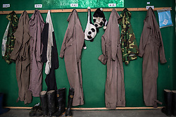 """Panda costumes that are worn by caretakers hang inside the<br />employee room at the Wolong Nature Reserve managed by the China<br />Conservation and Research Center for the Giant Panda. Babies are born<br />in a quiet moss and as they grow they are moved to progressively<br />bigger, more complex and """"wilder"""" enclosures, eventually learning to<br />climb and forage for themselves. From birth,a panda slated for release<br />will never see a human, its training administered equally by its<br />mother and its unseen keepers in panda costumes."""