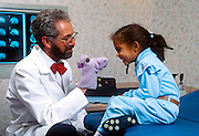 Doctor comforts young patient with a hand puppet.
