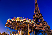 A low angle view of a carousel and the Eiffel Tower, the world famous wrought-iron lattice tower that is the most famous landmark of Paris, France.