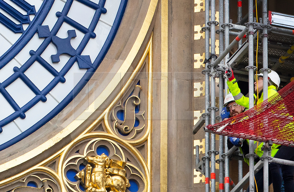© Licensed to London News Pictures. 20/03/2019. London, UK. A workman inspects the Elizabeth Tower clock face as it is revealed in its new Prussian Blue colour replacing the familiar black paint. Big Ben's north face is the first of the four famous clock faces to be seen in the original colour scheme from when it was built in 1859 by Sir Charles Barry. These works form part of a Parliamentary £61m restoration project which will also see the St George's shields at top of the clock face painted red and white for the first time since the 1930's.  Photo credit: Peter Macdiarmid/LNP