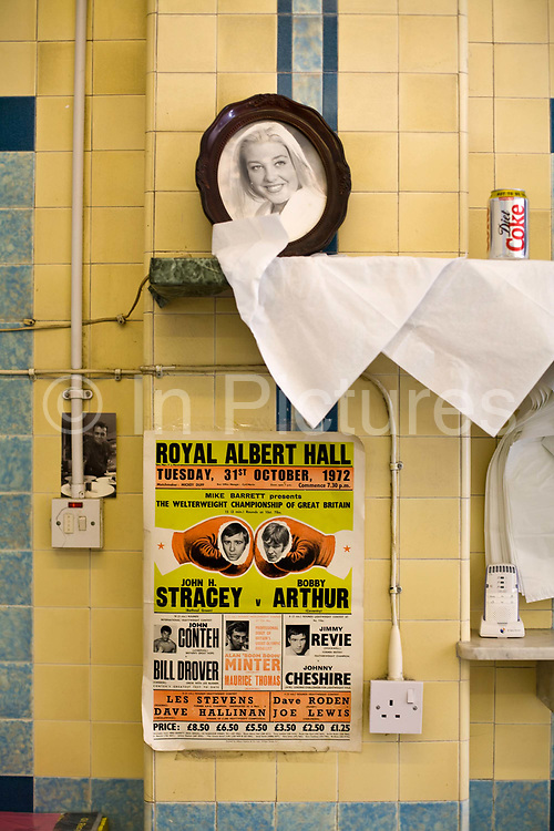 An old boxing poster on the wall of F Cooke's Pie and Mash shop in Broadway Market, Hackney, London..Eel, pie and mash shops are a traditional but dying business. Changing tastes and the scarcity of the eel has meant that the number of shops selling this traditional working class food has declined to just a handful mostly in east London. The shops were originally owned by one or two families with the earliest recorded, Manze's on Tower Bridge Road being the oldest surviving dating from 1908. Generally eels are sold cold and jellied and the meat pie and mash potato covered in a green sauce called liquor.
