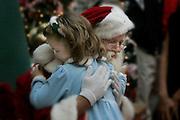 Santa and child embrace.