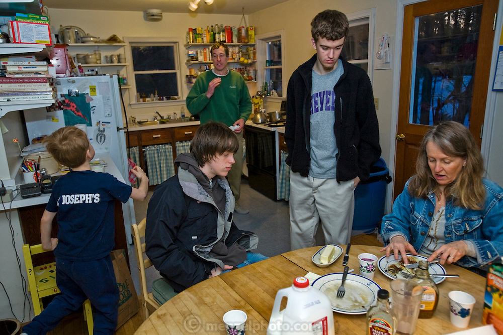 Karen Tucker, the lobsterman Samuel Tucker's wife, discusses morning logistics with her family over pancakes before heading to the ferry with her sons at Great Diamond Island, Maine..  (From the book What I Eat: Around the World in 80 Diets.) MODEL RELEASED.