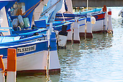 Typical Provencal fishing boats painted in bright colours white, blue, green red yellow, moored at the keyside Sanary Var Cote d'Azur France
