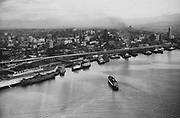 Viewed from the air over Elliott Bay, the Alaskan Way Viaduct appears to underline Seattle's skyline Dec. 26, 1951. In the foreground, a Princess ship from Canadian Pacific Lines heads to its pier. Smith Tower is the tall building at far right. (Larry Dion / The Seattle Times)