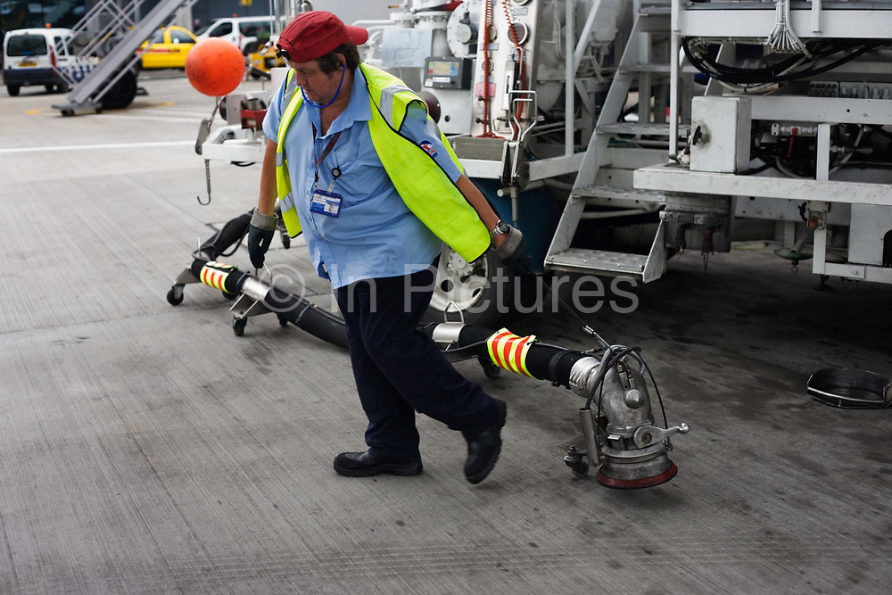 "During the turnround of the British Airways jet aircraft, a refueller drags the heavy fuel nozzle from his bowser truck on the apron at Heathrow Airport's Terminal 5. He is about to plug the connections into the airfield's underground reservoirs from where some 109 tons of Jet A1 aviation fuel flowing at a rate of 3,000 litres a minute will be uplifted into the wing tanks of a Boeing 747-300, a typical quantity of extra fuel for this aeroplane bound for Los Angeles. From writer Alain de Botton's book project ""A Week at the Airport: A Heathrow Diary"" (2009)."