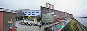 Nederland, Nijmegen, 5-1-2020 Het vroegere fabriekscomplex van de Honig fabriek. Het Honigcomplex is een tijdelijk bedrijfsverzamelgebouw gevestigd in de voormalige Honigfabriek in Nijmegen. Het gebouw huisvest 150 culturele en ambachtelijke bedrijfjes. Het complex met de beeldbepalende meelsilo en het bekende logo staat op de nominatie om in 2022 te worden gesloopt ten behoeve van woningbouw. Het oudste deel en de silo worden behouden . . De gemeente wilde het fabrieksterrein gebruiken voor woningbouw, nieuwbouw woningen. Door de kredietcrisis en de crisis op de woningmarkt is dit plan in 2012 uitgesteld en is het voor een aantal jaren aangewezen als een broedplaats en smeltkroes voor culturele en creatieve activiteiten en ondernemingen waaronder galerie Bart, muziekcafe Brebl . Ook horeca zoals restaurant de Meesterproef en bierbrouwer Oersoep . De nieuwe waalbrug, brug over de Waal De Oversteek ligt hiet vlakbij rechts op de foto . Foto: Flip Franssen