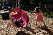 Children play with rope swing in risk averse playground called The Land on Plas Madoc Estate, Ruabon, Wrexham, Wales.