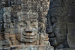 Tight image of two Buddha heads, one light, another dark... facing the lighter one