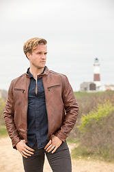 handsome man outdoors in a leather jacket by a lighthouse