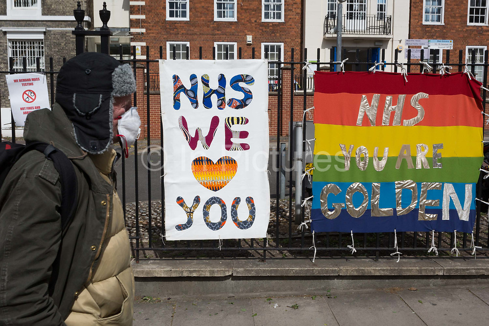 The day after UK Prime Minister Boris Johnson addressed the nation with his roadmap for the coming weeks and months during the Coronavirus pandemic lockdown, a man wearing a face mask walks past banners supporting and thanking NHS National Health Service key workers, outside the Maudsley Hospital that specialises in mental health services and is opposite Kings College Hospital one of the capitals major trauma centres and a site for Covid patients, on 11th May 2020, in London, England.