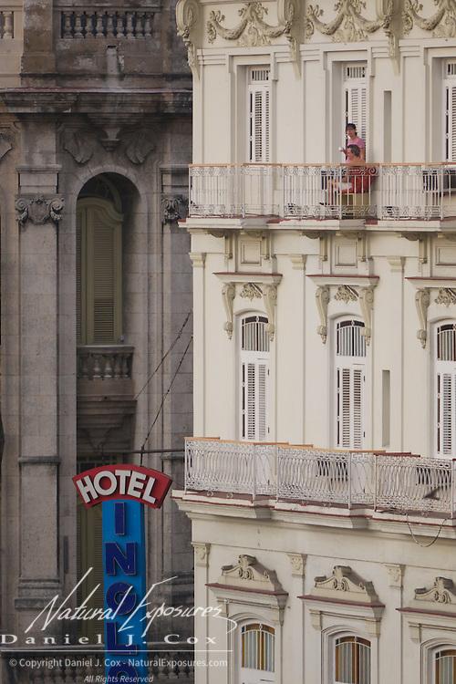 People enjoying the balcony of their hotel in downtown Havana, Cuba.