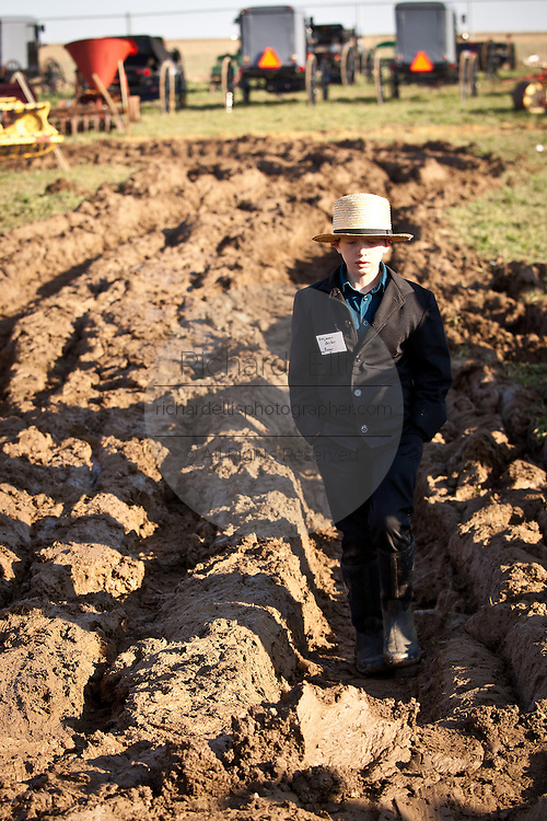 Young Amish boy walks through the mud during the Annual Mud Sale to support the Fire Department  in Gordonville, PA.