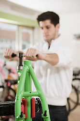 Young man working on bicycle frame