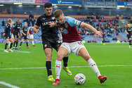 Burnley defender Ben Gibson (14) holds back Barnsley midfielder Alex Mowatt (27) during the The FA Cup 3rd round match between Burnley and Barnsley at Turf Moor, Burnley, England on 5 January 2019.