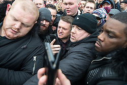 """© Licensed to London News Pictures . 18/03/2018 . London , UK . TOMMY ROBINSON (centre) is pushed through the crowd as he leaves . 1000s including supports of alt-right groups such as Generation Identity and the Football Lads Alliance , at Speakers' Corner in Hyde Park where Tommy Robinson reads a speech by Generation Identity campaigner Martin Sellner . Along with Brittany Pettibone , Sellner was due to deliver the speech last week but the pair were arrested and detained by police when they arrived in the UK , forcing them to cancel an appearance at a UKIP """" Young Independence """" youth event , which in turn was reportedly cancelled amid security concerns . Photo credit: Joel Goodman/LNP"""