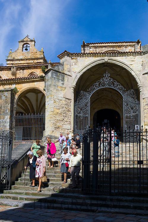Roman Catholic worshippers leaving Mass in the church Iglesia Santa Maria de la Asuncion, Laredo, Cantabria, Spain