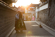 A couple dressed in Hanboks, traditional Korean clothing, kiss in Bukchon Hanok Village on 26th February 2018 in South Korea. The Bukchon Hanok Village is a Korean traditional village in Seoul with a long history located between Gyeongbok Palace, Changdeok Palace and Jongmyo Royal Shrine