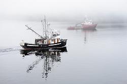 Fishing boats slowly make their way through the fog in Auke Bay near Juneau, Alaska.