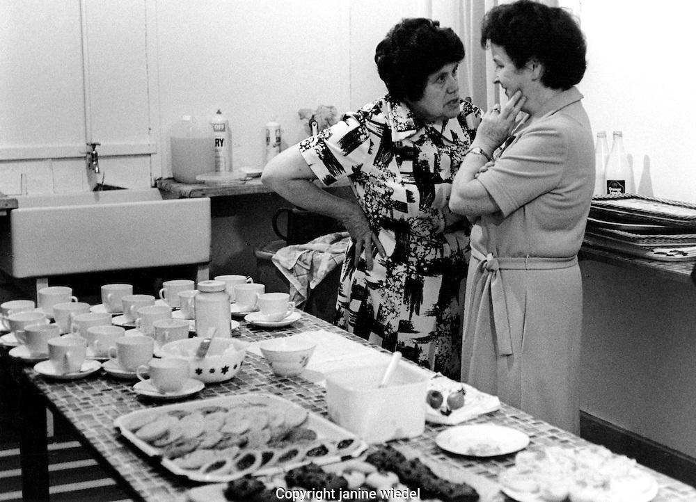 two women gossiping while preparing tea for afternoon local event.