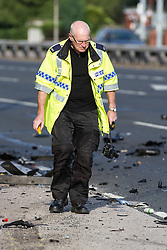 © Licensed to London News Pictures . 22/06/2014 . Manchester , UK . Fatal RTA scene in Manchester where a man has died in a three vehicle collision on the East Lancs Road (A580) this afternoon (Sunday 22nd June 2014) . An Audi RS3 and an Audi S3 were travelling eastbound along the A580 when they collided with a Vauxhall Corsa , near to the Swinton Park area . The male driver of the Corsa suffered multiple injuries and was pronounced dead at the scene . A woman passenger also suffered serious injuries and has been taken to hospital in a critical condition . The drivers of the Audis - two men - are under arrest on suspicion of causing death by dangerous driving and are in police custody . Photo credit : Joel Goodman/LNP