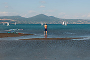 A man stands in the lands emerged because of the low water level of Bracciano lake on July 28, 2017 in Rome, Italy. Rome has suffered from worsening drought since March so as of tomorrow the municipality has decided to take action and ration the distribution of water to citizens, with 8 hour delivery blocks to each area. ©Simone Padovani