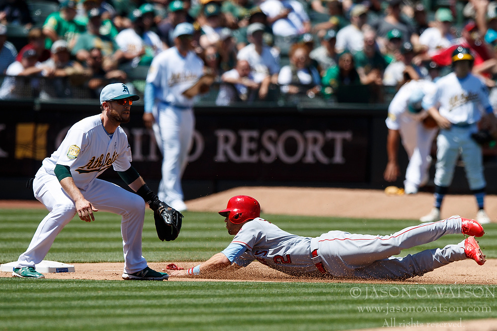 OAKLAND, CA - JUNE 17: Andrelton Simmons #2 of the Los Angeles Angels of Anaheim dives into third base past Jed Lowrie #8 of the Oakland Athletics during the sixth inning at the Oakland Coliseum on June 17, 2018 in Oakland, California. The Oakland Athletics defeated the Los Angeles Angels of Anaheim 6-5 in 11 innings. (Photo by Jason O. Watson/Getty Images) *** Local Caption *** Andrelton Simmons; Jed Lowrie
