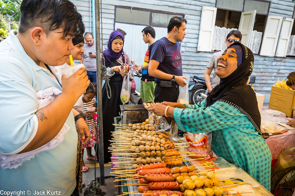 "08 AUGUST 2013 - BANGKOK, THAILAND:       A food vendor sells grilled halal meats at an outdoor market next to Haroon Mosque after Eid al-Fitr services. Eid al-Fitr is the ""festival of breaking of the fast,"" it's also called the Lesser Eid. It's an important religious holiday celebrated by Muslims worldwide that marks the end of Ramadan, the Islamic holy month of fasting. The religious Eid is a single day and Muslims are not permitted to fast that day. The holiday celebrates the conclusion of the 29 or 30 days of dawn-to-sunset fasting during the entire month of Ramadan. This is a day when Muslims around the world show a common goal of unity. The date for the start of any lunar Hijri month varies based on the observation of new moon by local religious authorities, so the exact day of celebration varies by locality.   PHOTO BY JACK KURTZ"