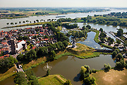 Nederland, Noord-Brabant, Woudrichem, 08-07-2010; vestingstad in Land van Heusden en Altena. Gelegen op de plaats waar de Maas (nu Afgedamde Maas) in de Waal stroomt en verder gaat als Boven-Merwede. In het centrum de  Martinuskerk, buiten de stadsmuren molen Nooit Gedagt (korenmolen)..Fortified town in Land of Altena. Located at the place where the Maas (Meuse) flows in the river Waal river, continuing under the name of Boven-Merwede. In the center church of Saint Martin, outside the city walls the mill Never thought fit (flour mill)..luchtfoto (toeslag), aerial photo (additional fee required).foto/photo Siebe Swart.