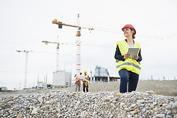 Female architect with digital tablet at construction site, Munich, Bavaria, Germany, Europe