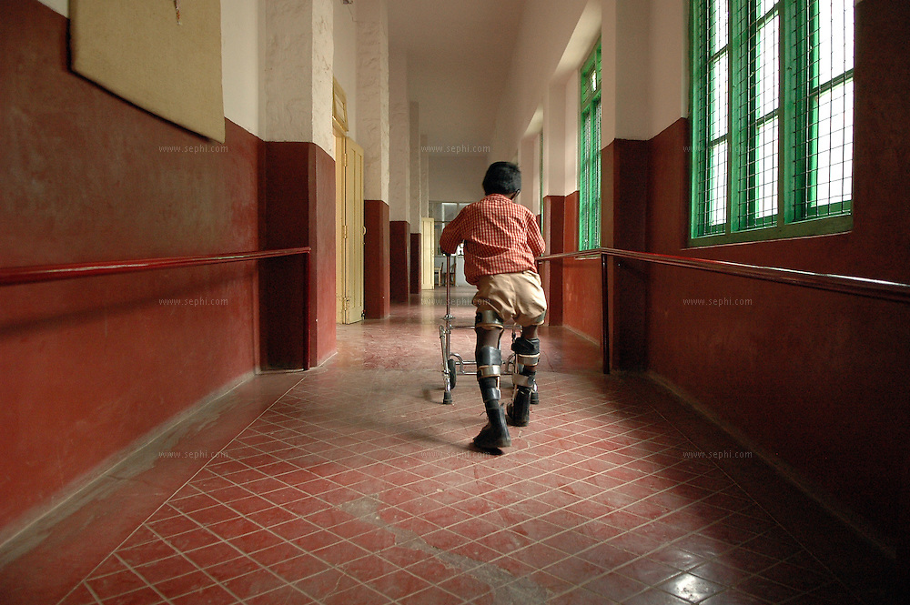 A disabled boy walks down the school corridor at APD School in Bangalore using a 'walker' made at APD manufacturing unit