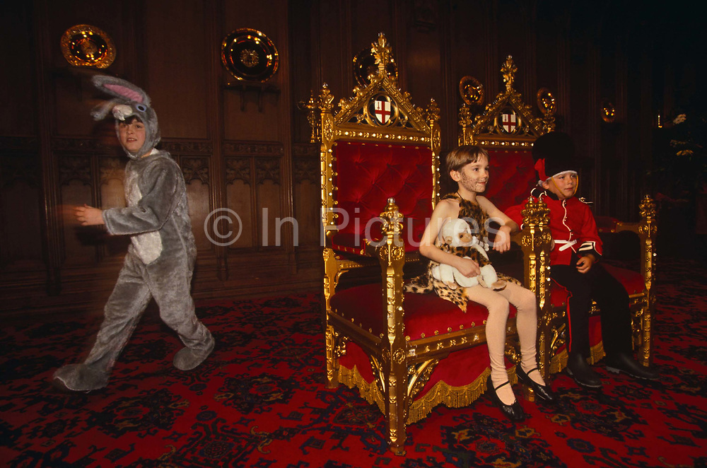 In the weeks before Christmas day on December 25th, the Lord Mayor of London hosts an annual party at his official town hall - the Guildhall - in the historic financial district of the City of London. Inviting Greater London's borough Mayors, they can each invite worthy children for an afternoon's fancy dress party. Two children dressed as Tarzan with a small monkey and a Grenadier Guard with a bearskin, and are seated on the Mayoral throne like two princes in a royal court. The chairs are coated with gold leaf with red cushioned fabric and with the Corporation of London's crest on the top. It looks resplendent and opulent. The two kids are sat looking small in the chairs seemingly made for giants but behind them is another boy dressed as a grey rabbit with floppy ears running past. The Guildhall has been used as a town hall for several hundred years, and is still the ceremonial centre of the City of London. The term Guildhall refers both to the whole building and to its main room, which is a medieval style great hall similar to those at many Oxbridge colleges. The Guildhall complex houses the offices of the Corporation of London and various public facilities. (Greater London also has a City Hall). The great hall is believed to be on the site of an earlier Guildhall, and has large mediaeval crypts underneath. During the Roman period it was the site of an amphitheatre, the largest in Britannia. The City of London is still part of London's city centre, but apart from financial services, most of London's metropolitan functions are centred on the West End. The City of London has a resident population of under 10,000 but a daily working population of 311,000.