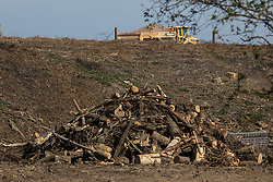 Calvert, UK. 26th April, 2021. A pile of trees felled for the HS2 high-speed rail link is viewed from the remainder of Calvert Jubilee Nature Reserve. Calvert has been particularly badly impacted by HS2 infrastructure project work because of its position close to the intersection between HS2 and East West Rail and a large section of Calvert Jubilee Nature Reserve has been destroyed.