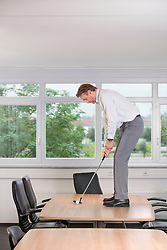 Office man concentrating Practising golf boss