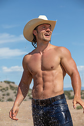 hot cowboy getting sprayed with water outdoors