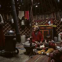 "CHINA. Xinjiang. Nomadic Kyrgyz women prepare tea and lamb fat for dinner inside felt-lined ""akoi"" (yurt) near Lake Karakul in Pamir Mountains."