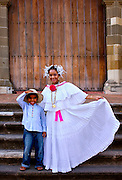 In the Casco Viejo neighborhood of Panama City a mother and son are dressed in the national costumes of Panama.  The mother is in a polerra dress for woman, and the boy is wearing a straw montuno hat and embroidered shirt for men.