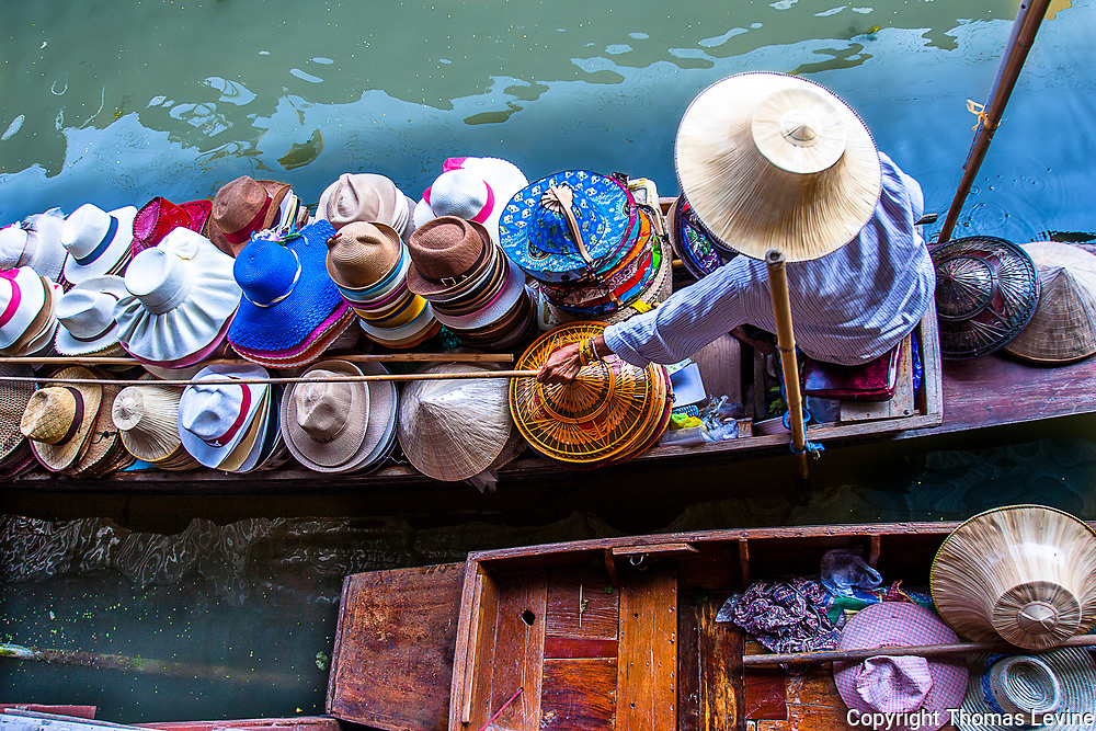 Fine Art<br /> Thai lady sells assorted hats from her boat at the floating Damnoen Saduak Floating Market, just outside of Bangkok, Thailand.