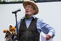 Wendover, UK. 9th May, 2021. A local resident makes a speech holding a fox toy at an event in Jones Hill Wood billed as an 'Accolade To The Ancients' in tribute to the ancient woodland there which is being felled for the HS2 high-speed rail link. The event featured a reading of an adaptation of Roald Dahl's Fantastic Mr Fox, which it is said he was inspired to write by Jones Hill Wood, as well as poems, speeches and face painting.