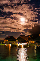 Overwater bungalows at night (by moonlight), Hilton Moorea Lagoon Resort, island of Moorea, French Polynesia.