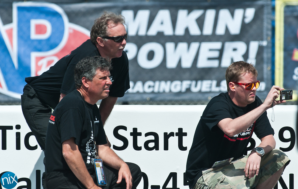 Ronnie Siani, Ken Griffiths and his son Kyle, watch their friend Chuck Westcott make a practice run at zMAX Dragway during the VisitMyrtleBeach.com NHRA Four-Wide Nationals Thursday morning.    (Photo by James Nix)