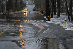 Falls River Flooding Across Dennison Road in Essex CT on 30 March 2010. At Dusk, Auto approaches the safety tape and sawhorse placed to keep traffic and people out and away from the swirling water over the road.