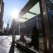 Cold travelers stay out of the wind as they await a bus at the bus stop in the Manhattan borough of New York on Thursday, Jan. 23, 2014. A recent snow storm created by a polar vortex, dumped almost a foot of snow in some areas of New York City, followed by bitter cold. The NFL plans on featuring the Super Bowl at MetLife stadium in New Jersey on February 3rd amid growing concerns about more snow and bitter cold arriving just prior to the game.  (AP Photo/Alex Menendez)