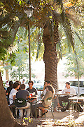 People relax in a cafe in the late afternoon at Praca do Principe Real, Lisbon, Portugal