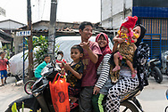 Jakarta, Indonesia - July 7, 2017: Two adults and three children ride together on a small motorbike in a neighborhood of Jakarta, Indonesia.