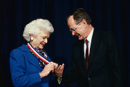 Washington, DC 1989/04/01 George and Barbara Bush look at a medal given to her by the Assoication of Communty Colleges.<br />Photo by Dennis Brack